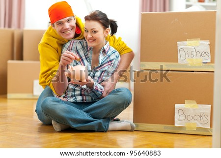 Young couple among boxes putting coin in piggy bank - stock photo
