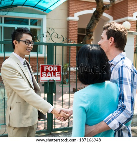 Young couple and broker making a deal - stock photo