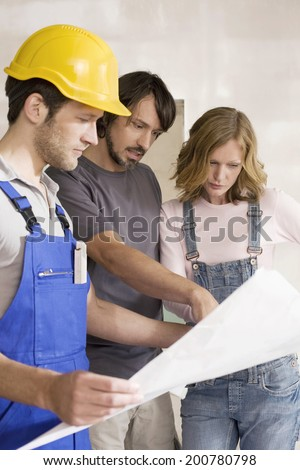 Young couple and construction worker looking at construction plan - stock photo