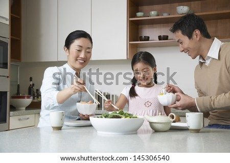 Young couple and daughter eating meal with chopsticks on kitchen counter - stock photo