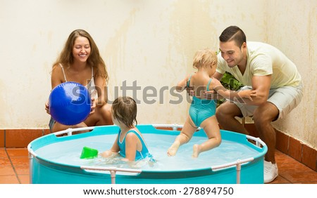 Young couple and little daughters having fun in pool outdoor. Focus on man - stock photo