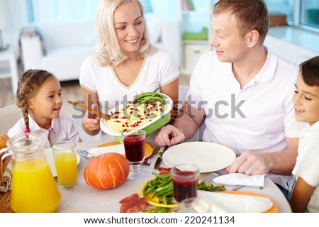 Young couple and their kids going to eat festive dinner at home - stock photo