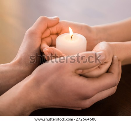 Young couple are holding hands and candle on the table. - stock photo