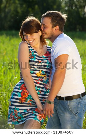 Young couple are on meadow on forest background. Girl and guy love each other. They are very funny. The guy has a watch on his arm.