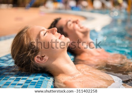 Young couple are relaxing in swimming pool. - stock photo