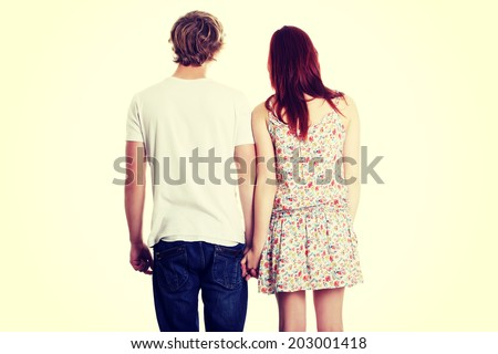 Young couple are standing a back side and holding hands. - stock photo
