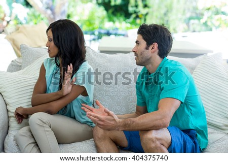 Young couple arguing on sofa at home - stock photo