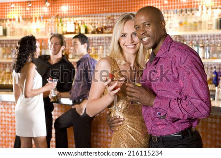 Young couple arm in arm in bar with drinks, smiling, portrait