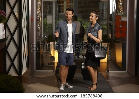 Young couple arriving at hotel lobby, having suitcases, smiling, looking for reception desk. - stock photo