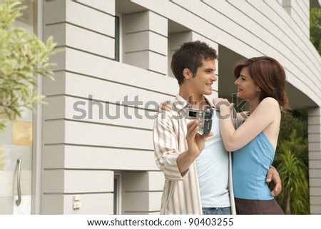 Young couple arriving at their new home and recording themselves at the house's entrance garden.