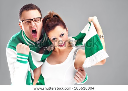 Young couple as supporters over gray background - stock photo