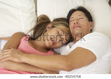 Young Couple Asleep In Bed - stock photo