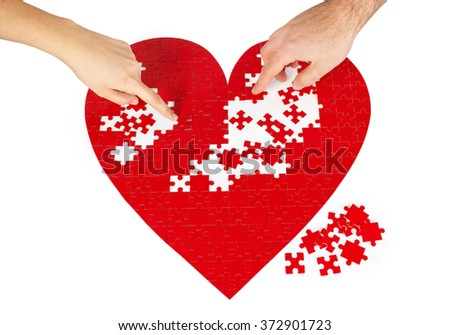 Young couple assembling a red puzzle heart shape on white background.