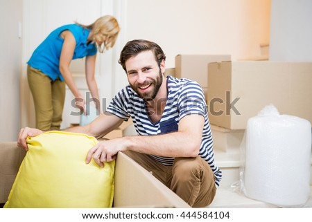 Young couple assisting each other while unpacking cartons in new house - stock photo
