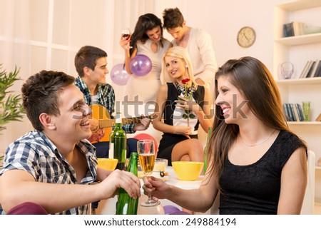 Young couple at a house party, sit on the floor and knocking with drinks, in the background you can see their friends, two couples. - stock photo