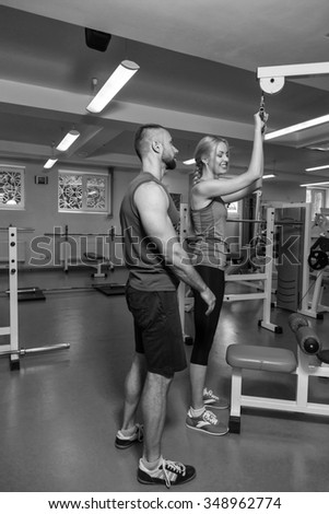Young couple at a joint training session in the gym. Mutual assistance in carrying out exercises. Proper exercise. Photos for sporting and social magazines, posters and websites.
