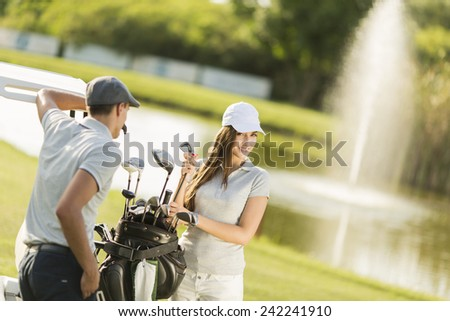 Young couple at golf court - stock photo
