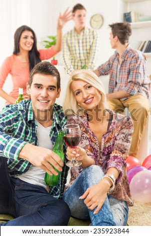 Young couple at home party, sit on the floor, knocking toasting with drinks, smiling looking at camera. In the background you can see their friends who are sitting on the couch. - stock photo