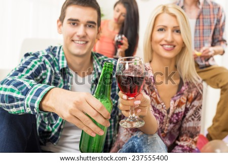 Young couple at home party with a smile on their faces out of focus, toasting with drinks that are in the foreground. In the background is another young couple. - stock photo