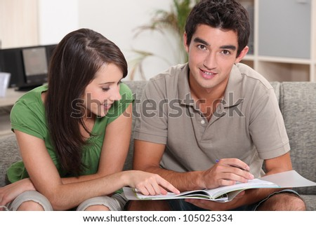 young couple at home skimming through catalogue - stock photo