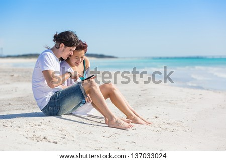 Young Couple at Seaside with Digital Tablet - stock photo