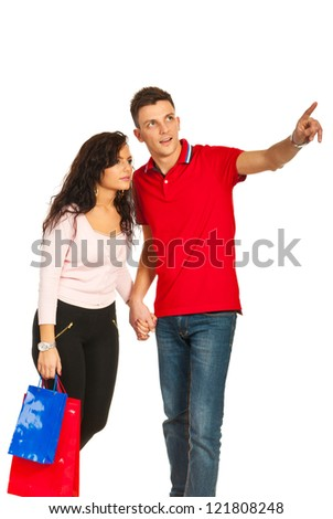 Young couple at shopping,man showing to woman something to copy space isolated on white background