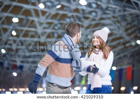 Young couple at skating rink - stock photo