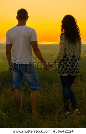 young couple at sunset on sky background, love concept, romantic people - stock photo