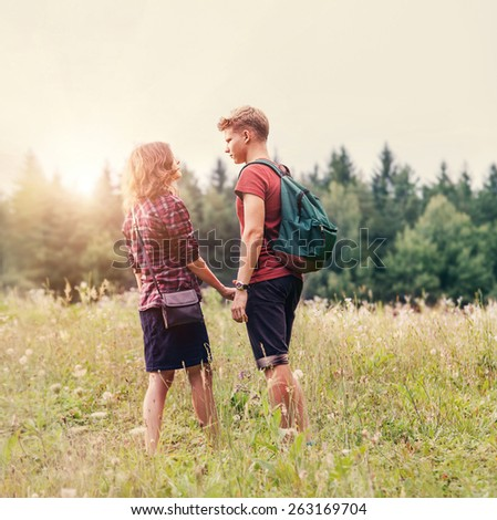 Young couple at sunset time on forest walk - stock photo
