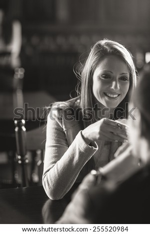 Young couple at the bar having a coffee and flirting - stock photo
