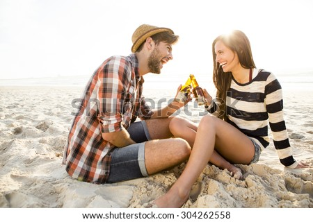 Young couple at the beach having fun, laughing and drinking beer - stock photo