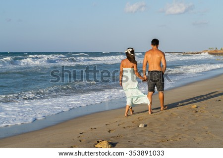 Young couple at the beach on a  hazy summer day at dusk, wearing a turquoise dress and shorts, enjoying  walking barefoot by the ocean water.