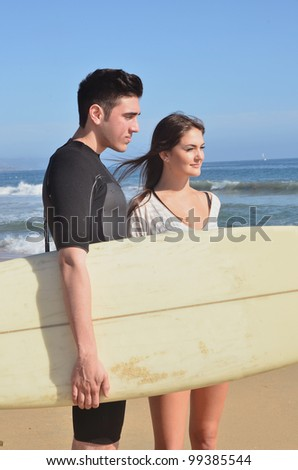 Young couple at the beach/Surfs Up/Young Couple enjoying the beach and surfing - stock photo