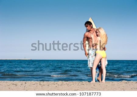 Young couple at the beach with surfboard with copy space.
