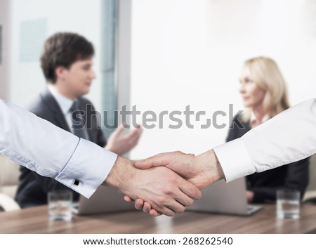 Young couple at the business meeting. Handshake as a concept of successful deal. - stock photo