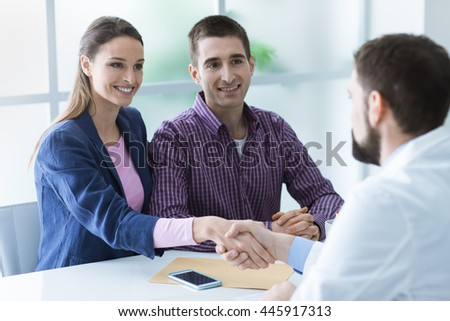 Young couple at the doctor's office during a visit, she is shaking the doctor's hand