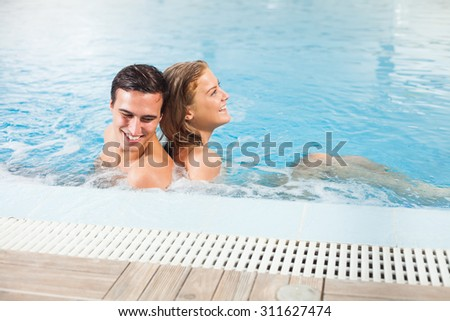 Young couple at the swimming pool enjoying hydro massage
