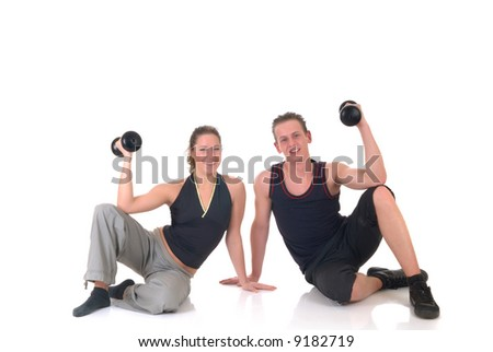 Young couple, attractive female, handsome male doing fitness exercises in the gym. Studio shot