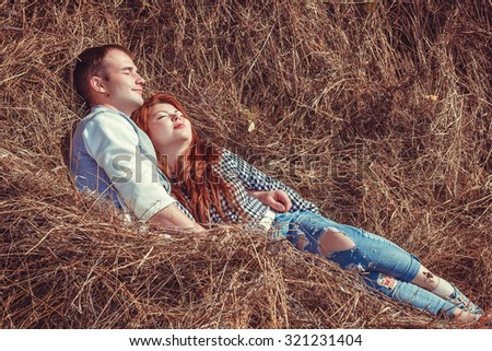 Young couple: attractive man and woman with red hair lying on a stack of hay, relaxing, embracing and enjoying the autumn sun. Photo with warm toning - stock photo