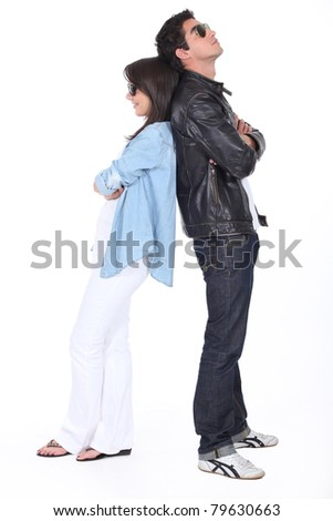 Young couple back to back in sunglasses and leather jacket - stock photo