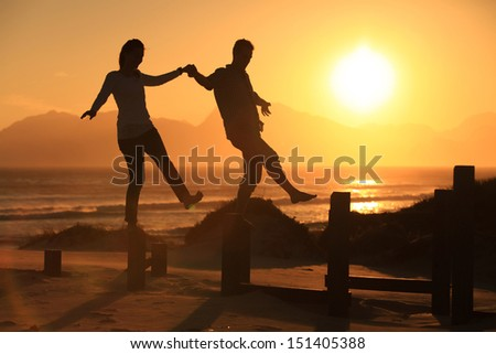 Young couple balancing on some pillars at sunset on the beach. - stock photo