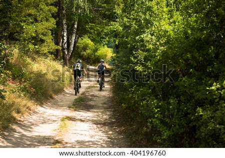 young couple biking on a trail track to the hill in the summer forest - stock photo