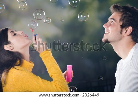Young couple blowing bubbles, outdoors - stock photo