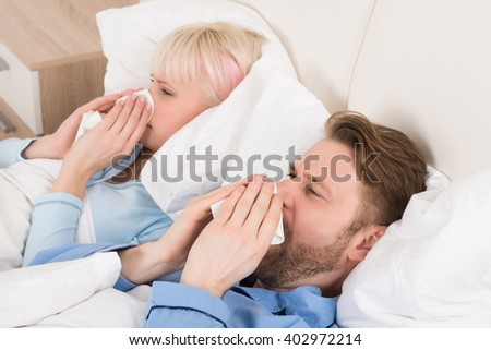 Young Couple Blowing Their Nose While Lying In Bed At Home - stock photo