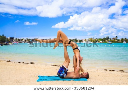 Young couple boy and girl practicing acroyoga exercises in the morning on the beach over sea background