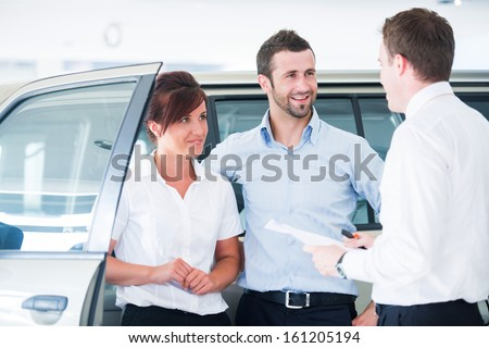 Young couple buying automobile from salesman in a car salon - stock photo
