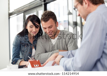 Young couple buying new home. Meeting with architect. - stock photo