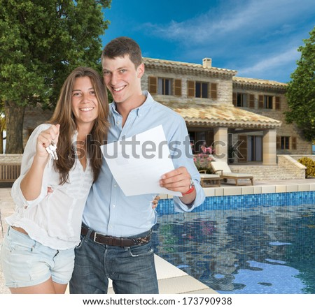 Young couple by a beautiful house with swimming pool holding a document and a bunch of keys - stock photo