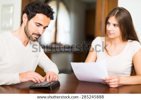 Young couple calculating their expenses. Shallow depth of field, focus on the man - stock photo