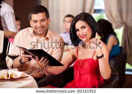 young couple calling waiter restaurant table - stock photo